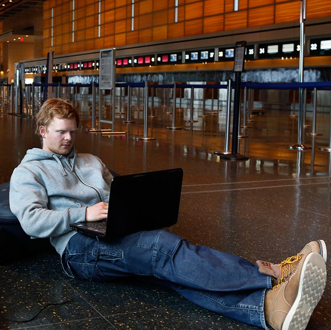 Rasmus Thomsen of Denmark works on his computer as he waits at Boston Logan International Airport.
