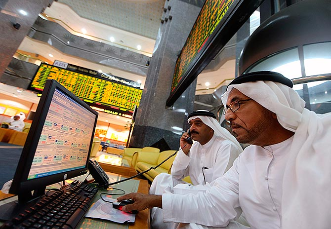 Investors monitor screens displaying stock information at the Abu Dhabi Securities Exchange.