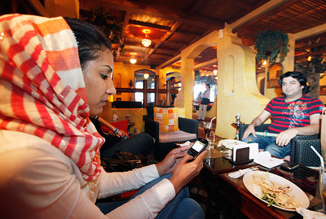 A woman checks her messages on her mobile phone at a coffeeshop.