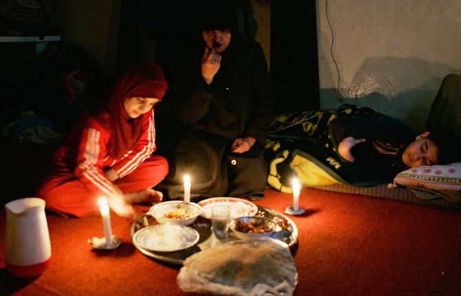 Iraqi migrant Ahlam al-Jibouri and her children eat a meal during a power outage.