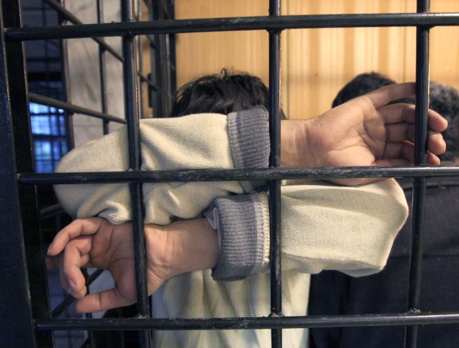 A detained illegal immigrant from a former Soviet republic waits in a holding cell at a police station in Russia's Siberian city.