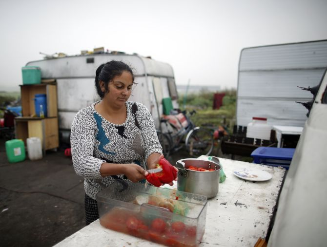A Roma woman cooks vegetables in front of caravans at an encampment of Roma families near Paris.
