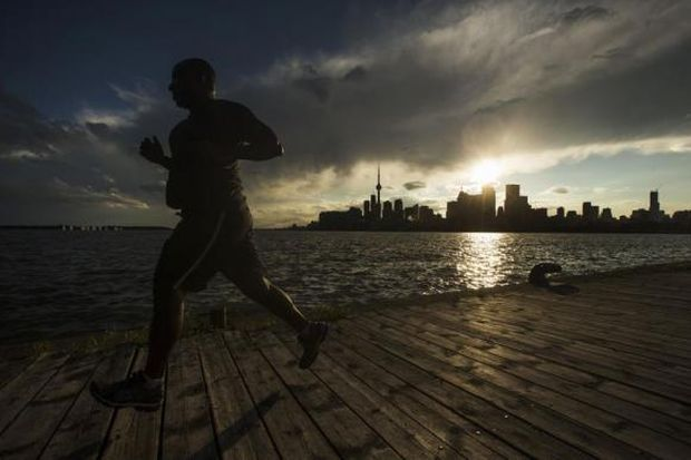 A man jogs in front of the skyline in Toronto.