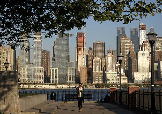 A woman walks along a promenade next to the Hudson River across from the skyline of New York in Weehawken, New Jersey.