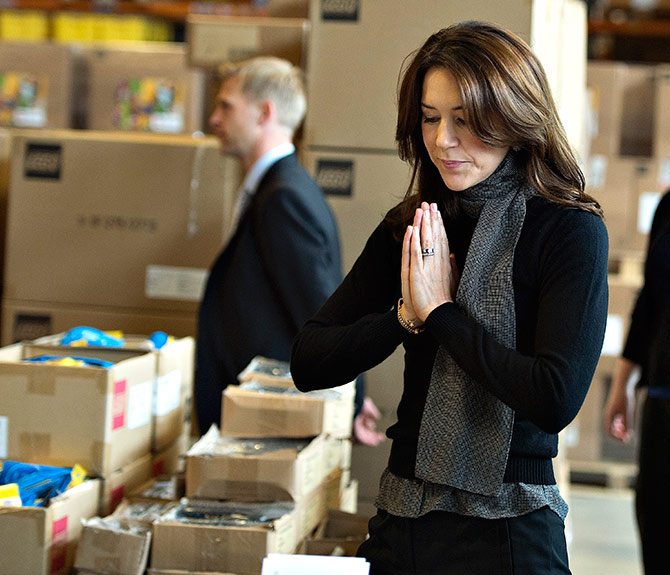 Denmark's Crown Princess Mary gestures as she helps former Lego employees with the annual packing of backpacks for children at women's shelters at Lego's Ole Kirk Foundation in Billund.