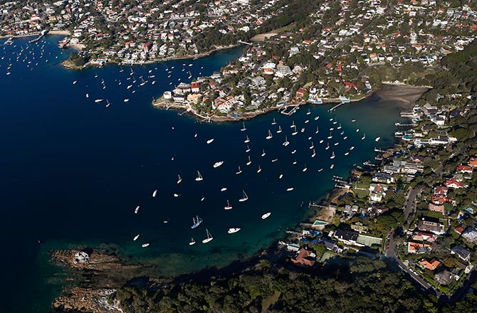 Boats are docked at Vaucluse bay (R) on a sunny winter afternoon in Sydney.
