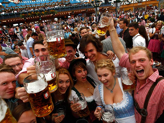 Visitors cheer with mugs of beer during the opening day the 180th Oktoberfest in Munich.