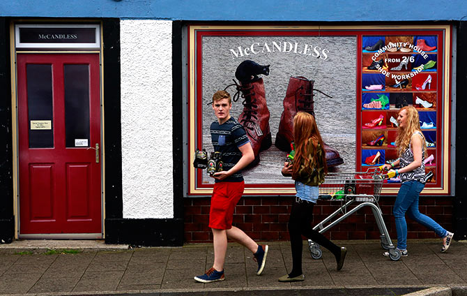 Youths walk past a shop, which has been covered with artwork to make it look more appealing, in the village of Bushmills on the Causeway Coast.