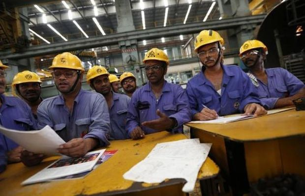 Employees check papers during their meeting after their lunch break inside the heavy electrical manufacturing unit of Larsen & Turbo in Mumbai.