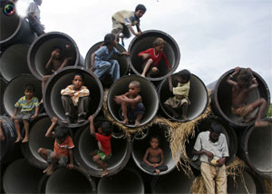 Image: Children play in water pipes at a construction site on the banks of the Yamuna River in Allahabad. Photograph: Jitendra Prakash/Reuters