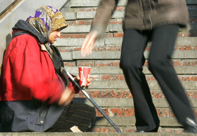 A person drops money into a container of a begging woman in Kiev.