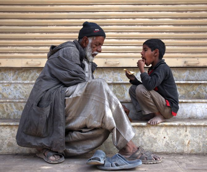 A man and child eat food that they begged for from a nearby food stall, outside a closed shop in Karachi.