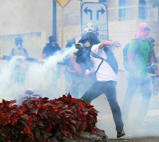 An anti-government protester throws a tear gas canister back at the police during a protest against the government.