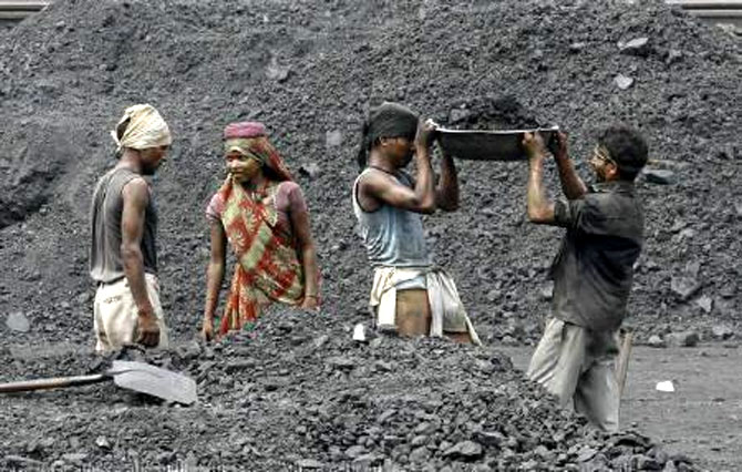 Laborers work in a railway coal yard on the outskirts of Ahmedabad. Photograph: Amit Dave/Reuters