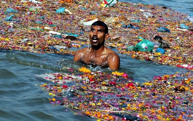 A man takes a dip in the polluted waters of river Ganga in Allahabad. Photograph: Jitendra Prakash