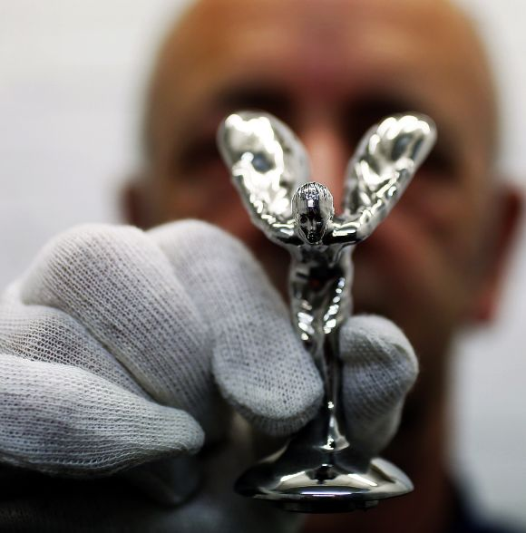 Worker Ronald Little poses with a finished Rolls-Royce mascot the Spirit of Ecstasy.