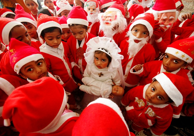 Children dressed in Santa Claus costumes gather around a girl dressed up as Virgin Mary during Christmas celebrations at a church in Chandigarh.