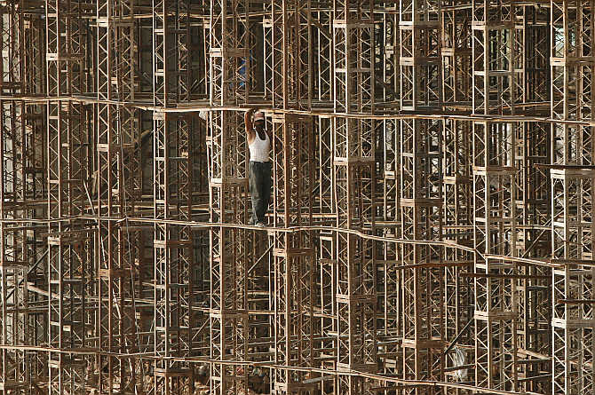 A construction worker stands on scaffolding on the outskirts of Jammu.