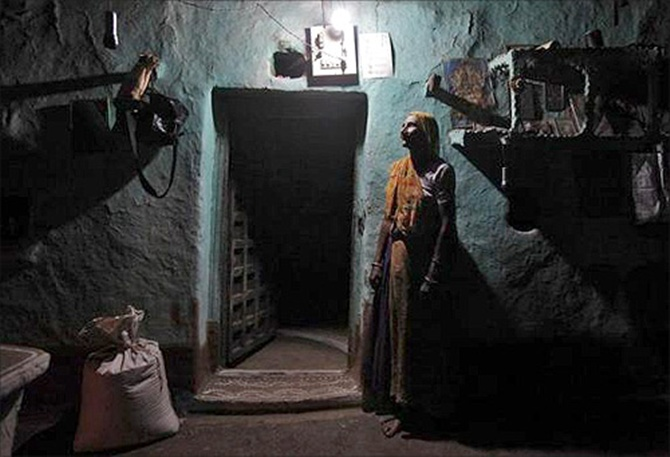 Sampat Bai, 64, poses for a picture inside her house illuminated by a Compact Fluorescent Lamp (CFL) that is powered by solar energy, at Meerwada village of Guna district, in Madhya Pradesh.