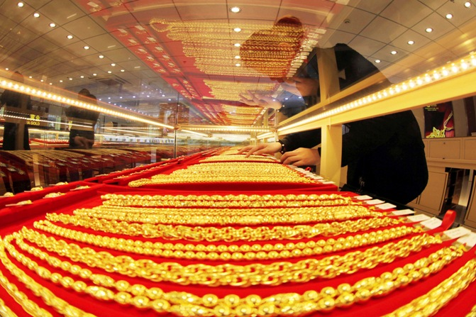 A sales assistant arranges gold necklaces at a store in Lianyungang, Jiangsu province.