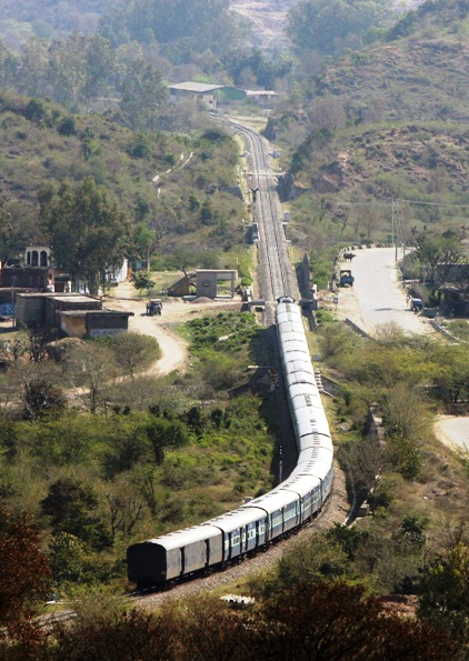 A passenger train moves along the Jammu-Udhampur rail line on the outskirts of Jammu.