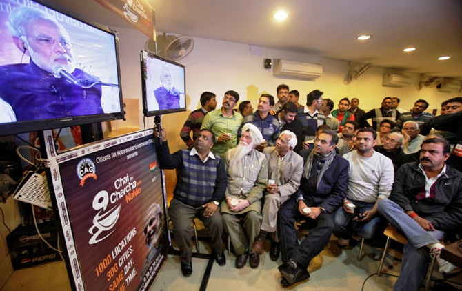 Supporters of Bharatiya Janata Party listen to Gujarat's chief minister Narendra Modi, the prime ministerial candidate for BJP, during a live video broadcast campaign on 'Talk over tea with Modi', in Chandigarh.