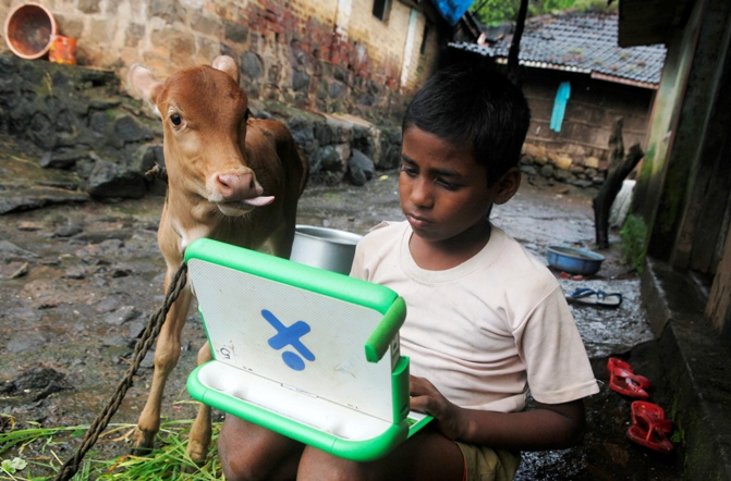 Harish, 11, a school boy uses a laptop provided under the 'One Laptop Per Child' project by a non-governmental organisation as a calf stands next to him, on the eve of International Literacy Day at Khairat village, about 90 km (56 miles) from Mumbai.