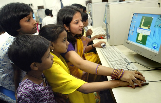 A trainer teaches Indian children how to use the computer in Kolkata.