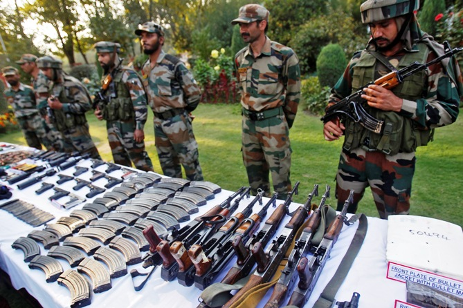 Indian army soldiers stand behind a display of seized arms and