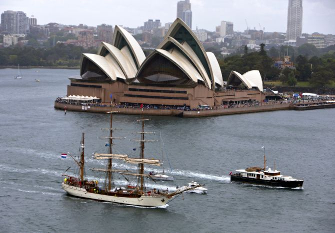 A tall ship sails past the Sydney Opera House as it enters Sydney Harbour.