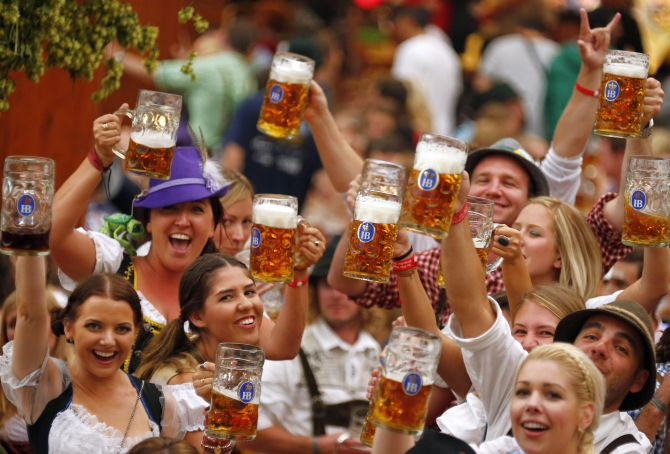 Revellers toast after getting the first beer in the traditional one-litre Masskrug beer mugs at the opening day of the Munich Oktoberfest at the Theresienwiese in Munich.