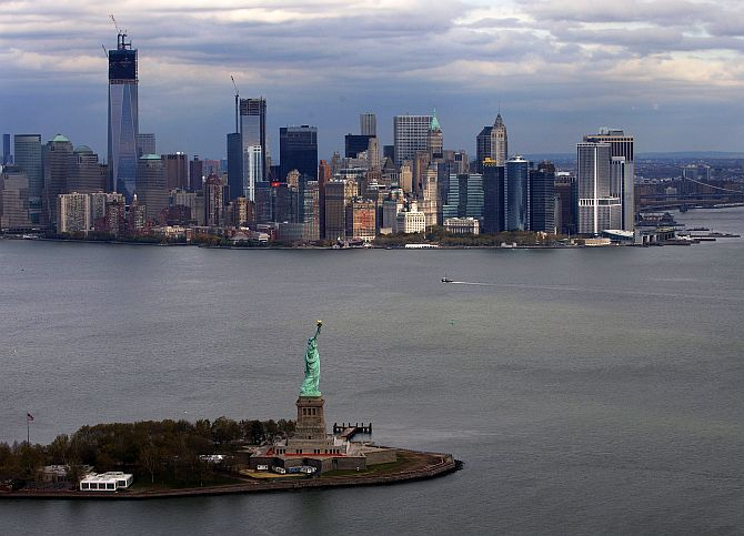 The Statue of Liberty and Liberty Island are seen in front of the Lower Manhattan skyline.