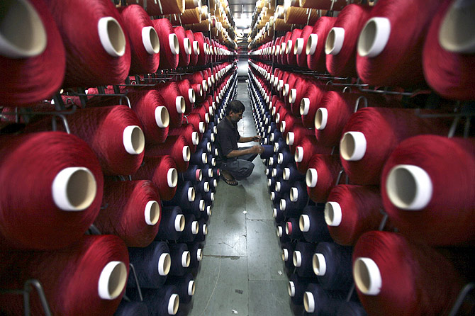 An employee works at the production line of a carpet manufacturing factory in Jammu