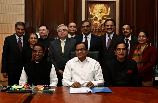 Finance Minister Palaniappan Chidambaram (C) sits with his staff before making the final touches to the interim budget for 2014/15 in New Delhi.