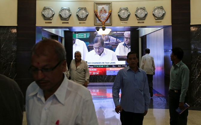 People walk in the lobby as a telecast of Finance Minister P Chidambaram presenting the interim budget is displayed inside the Bombay Stock Exchange building in Mumbai February 17, 2014.