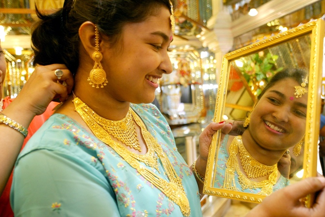 This file photographs shows a woman trying gold ornaments on the occasion of the Hindu festival of Dhanteras in Kolkata.