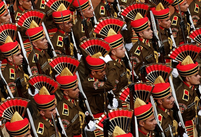 A policeman (C) adjusts his headgear as he marches with others during the full dress rehearsal for the Republic Day parade in New Delhi January 23, 2014.