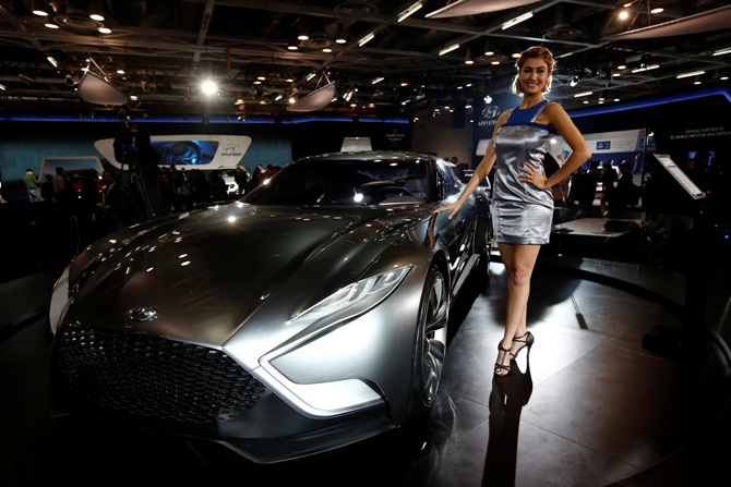 A model stands next to a Hyundai HND-9 Venace concept car during the Indian Auto Expo in Greater Noida on the outskirts of New Delhi, February 5, 2014.