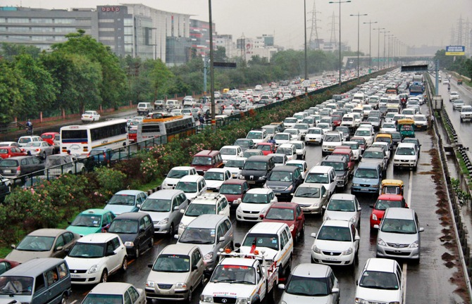 Heavy traffic moves along a busy road as it rains at the toll-gates at Gurgaon on the outskirts of New Delhi.