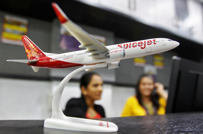 Employees work inside a travel agency office besides a model of a SpiceJet aircraft in Ahmedabad.