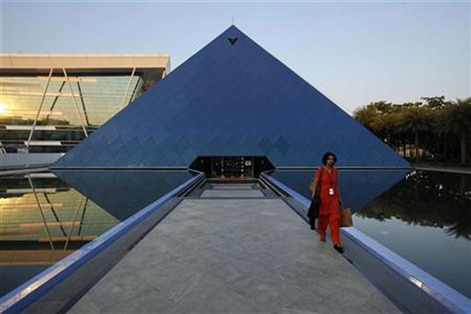 An employee walks out of an iconic pyramid-shaped building made out of glass in the Infosys campus at Electronics City in Bengaluru.
