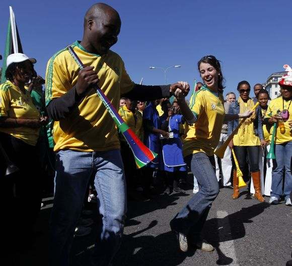 South Africans dance as they cheer during a parade to support the South African soccer team.