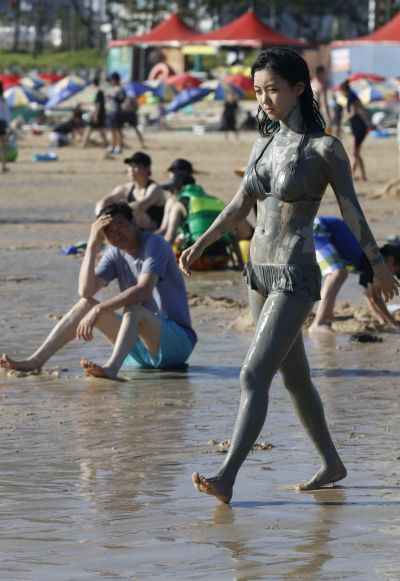 A woman walks on the beach to go swimming after playing in the mud during the Boryeong Mud Festival.