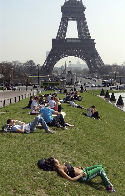 People relax in the sun near the fountains at Trocadero square near the Eiffel tower.