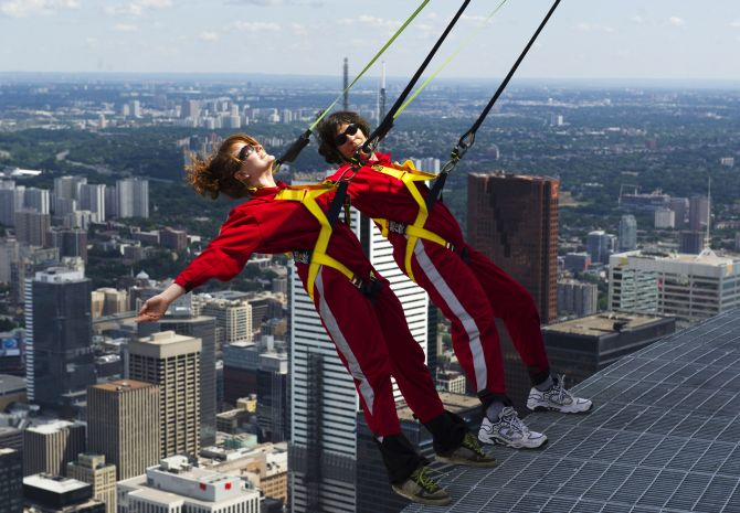 Reporters lean over the edge of the catwalk during the media preview for the EdgeWalk on the CN Tower in Toronto.