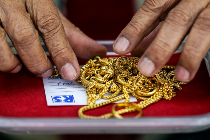 A pawn shop worker sorts through gold jewellery at Easy Money Pawn shop in Bangkok.