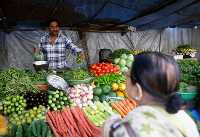 A customer speaks to a vendor while buying vegetables from a street side shop in Mumbai.