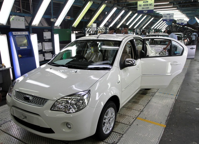 Workers make final inspections on Figo cars lined up at the assembly line at a plant of Ford India in Chengalpattu in the outskirts of Chennai.