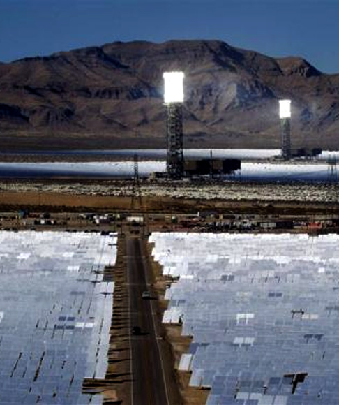 Heliostats reflect sunlight onto boilers in towers during the grand opening of the Ivanpah Solar Electric Generating System in the Mojave Desert near the California-Nevada border.