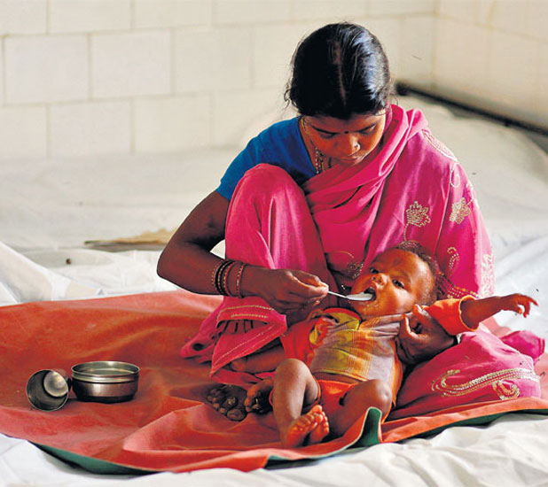 A woman feeds her malnourished child in Sheopur district. Most welfare programmes in India are corruption-ridden and poorly run.